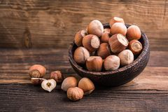 Raw hazelnuts. In wooden bowl on wooden background Stock Image