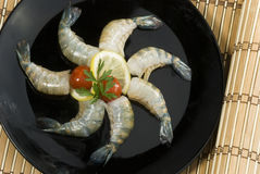 Raw head less shrimps with baby tomato lime and parsley on black plate Royalty Free Stock Image
