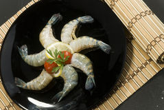 Raw head less shrimps with baby tomato lime and parsley on black plate Stock Photos