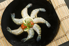 Raw head less shrimps with baby tomato lime and parsley on black plate Royalty Free Stock Photos