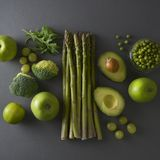 Raw healthy food clean eating vegetables: asparagus, cucumber, basil, green peas, avocado, broccoli, lime, apples, grapes,. Raw healthy food clean eating stock photo