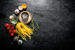 Raw home cooked pasta with spices, egg, oil and tomatoes. On black rustic background stock image