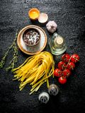 Raw home cooked pasta with spices, egg, oil and tomatoes. On black rustic background stock images