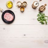 Raw homemade burgers in  pan with spices, herbs, potatoes and butter on rustic white wooden table border place for text Royalty Free Stock Images