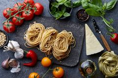 Raw homemade italian pasta cooking process. Raw homemade italian pasta and ingredients on white wooden background, cooking process Royalty Free Stock Images