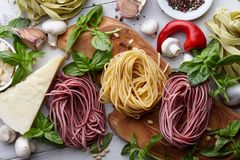 Raw homemade italian pasta cooking process. Raw homemade italian pasta and ingredients on white wooden background, cooking process Royalty Free Stock Photos