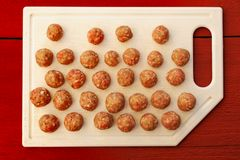 Raw homemade meatballs on white plastic board on red table Royalty Free Stock Photos