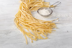 Raw homemade noodles with flour sieves on light wooden table. Raw homemade noodles with flour sieves on light rustic wooden table close up Royalty Free Stock Photo