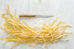 Raw homemade noodles with knife on a white background. Top view Royalty Free Stock Photos