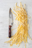 Raw homemade noodles with a large kitchen knife. On a white background, top view Royalty Free Stock Photo