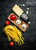 Raw homemade pasta with different sauces and Parmesan. On black rustic background stock photo