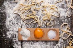 Raw homemade pasta with with egg yolk. Top view on raw homemade pasta with flour, sea salt and raw egg yolk over old wooden table. See series Royalty Free Stock Image