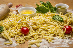 Raw homemade pasta with fresh herbs , tomatoes, flour, rolling pin ,egg and olive oil on rustic wooden background close up Royalty Free Stock Image