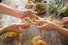 Raw homemade pasta and hands. Over wooden background Royalty Free Stock Image