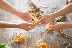 Raw homemade pasta and hands. Over wooden background Stock Image