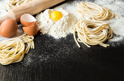 Raw homemade pasta. With ingredients on black background. Selective focus Stock Image