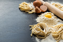 Raw homemade pasta. With ingredients on black background. Selective focus Stock Photo