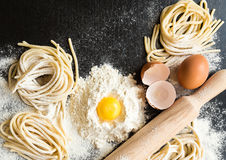 Raw homemade pasta. With ingredients on black background. Top view Stock Photos