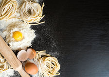 Raw homemade pasta. With ingredients on black background. Top view Royalty Free Stock Image