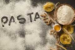 Raw homemade pasta and ingredients for integral pasta on wooden. Background Royalty Free Stock Images