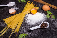 Raw homemade pasta and ingredients for pasta. On black background Stock Photos