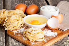 Raw homemade pasta and ingredients for pasta. Close up, horizontal Royalty Free Stock Photo