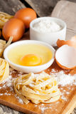 Raw homemade pasta and ingredients for pasta. Close up, vertical Royalty Free Stock Images