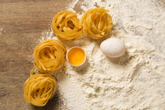 Raw homemade pasta and ingredients for pasta on wooden backgroun. D Stock Images