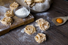 Raw homemade pasta and ingredients for pasta. On a wooden background Stock Image