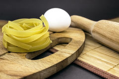Raw homemade pasta and ingredients for pasta. On wooden background Stock Photography