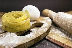 Raw homemade pasta and ingredients for pasta. On wooden background Stock Photos