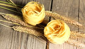 Raw homemade pasta and ingredients for pasta on wooden background.  Stock Photos
