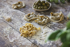 Raw homemade pasta and olives in plate on the old wooden table. Raw homemade pasta on the old wooden table. Traditional Italian food Stock Photos