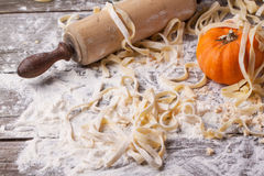 Raw homemade pasta with pumpkin. Flour and vintage rolling pin over old wooden table. See series Royalty Free Stock Photos