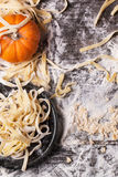 Raw homemade pasta with pumpkin. Top view on raw homemade pasta with pumpkin and flour over old wooden table Stock Photo