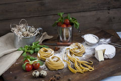 Raw homemade pasta, quail easter eggs in a aluminum cup, green lettuce, tomatoes and flour on wooden table Stock Image