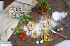 Raw homemade pasta, quail easter eggs in a aluminum cup, green lettuce, tomatoes and flour on wooden table Stock Photography