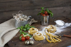 Raw homemade pasta, quail easter eggs in a aluminum cup, green lettuce, tomatoes and flour on wooden table Stock Photos