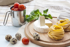 Raw homemade pasta, quail easter eggs in a aluminum cup, green lettuce, tomatoes and flour on wooden table Stock Photo
