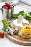 Raw homemade pasta, quail easter eggs in a aluminum cup, green lettuce, tomatoes and flour on wooden table Royalty Free Stock Photo