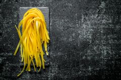 Raw homemade pasta on a stone Board. On rustic background stock photo