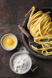 Raw homemade pasta tagliatelle. Raw uncooked homemade italian pasta tagliatelle with pasta cutter, bowls with white flour and broken egg in old clay tray over Royalty Free Stock Photos