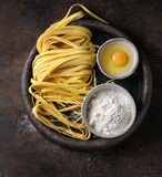 Raw homemade pasta tagliatelle. Raw uncooked homemade italian pasta tagliatelle with pasta cutter, bowls with white flour and broken egg in old clay tray over Stock Images