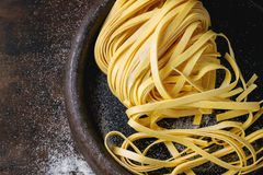 Raw homemade pasta tagliatelle. Raw uncooked homemade italian pasta tagliatelle with flour in old clay tray over dark wooden background. Top view with space for Royalty Free Stock Photo