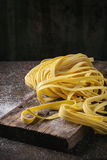 Raw homemade pasta tagliatelle. Raw uncooked homemade italian pasta tagliatelle with flour on old wood cutting board over dark wooden background. Side view with Royalty Free Stock Photos