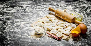 Raw homemade ravioli with egg, flour and a rolling pin. Royalty Free Stock Images