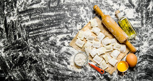Raw homemade ravioli with egg, flour and a rolling pin. Royalty Free Stock Photography