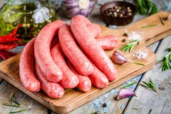 Raw homemade sausages on cutting board  with rosemary and garlic Royalty Free Stock Photo