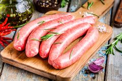 Raw homemade sausages on cutting board  with rosemary Stock Photography