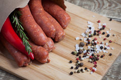 Raw homemade sausages of lamb with rosemary and chili pepper in a paper envelope, on a bamboo cutting Board Stock Photo